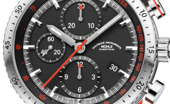 The chronograph hands are highlighted in red, matching the numerals on the tachymeter scale.